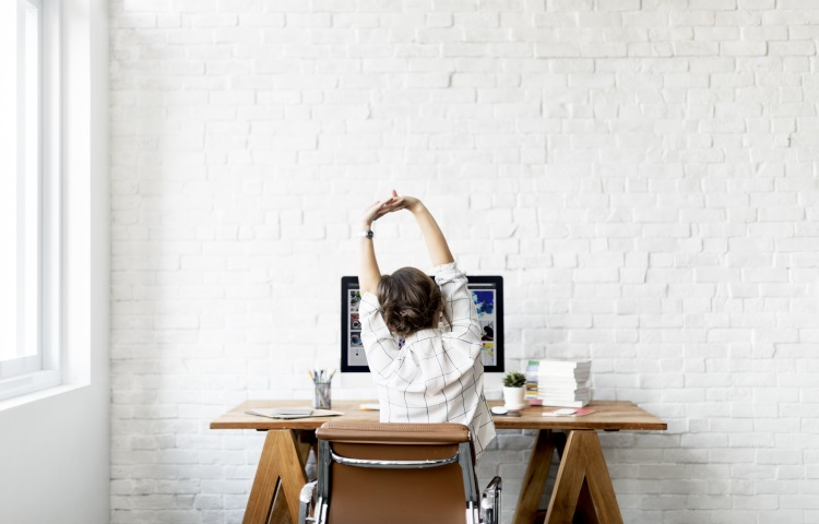 Woman stretching at work desk